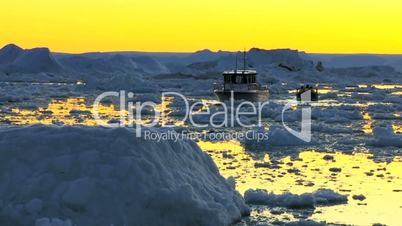 Nautical vessel at sunset in ice floes with icebergs