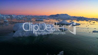 Sun setting over a polar iceberg