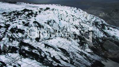 Aerial view of an Ice glacier dusted with black Volcanic ash, Iceland