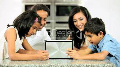 Young Ethnic Family with Wireless Tablet in Kitchen