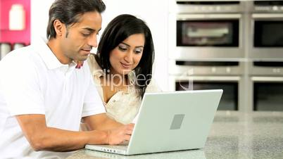 Asian Couple with Laptop Having Online Success