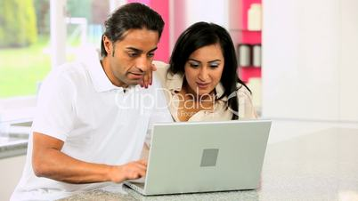 Ethnic Couple with Laptop Having Online Success