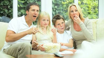 Attractive Family Enjoying TV & Popcorn