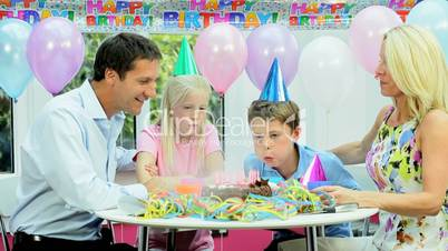 Young Caucasian Boy Blowing Out Birthday Candles