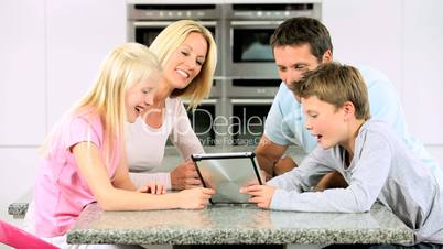 Young Family with Wireless Tablet in Kitchen