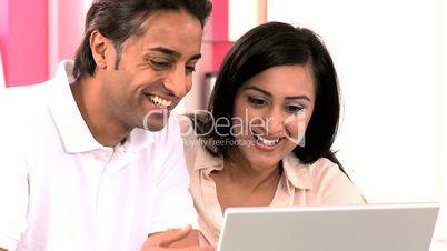 Attractive Young Ethnic Couple Using Laptop