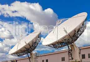 Satellite TV antenna on blue sky and clouds background