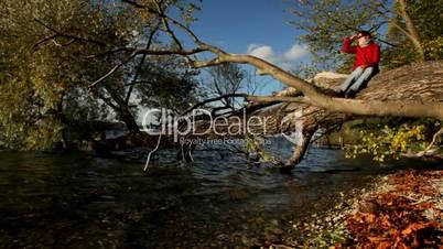 Starnberger See: Frau sitzt auf einem Baum im Wasser, Herbststimmung