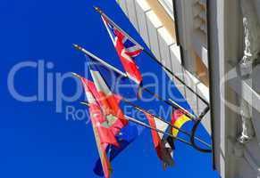 Flaggen und Fahnen an einem Gebäude im Wind vor blauen Himmel