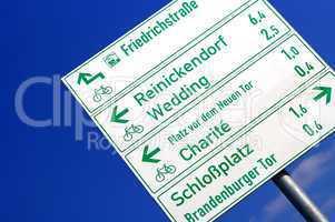 Straßenschild und Wegweiser in Berlin mit Schrift und Pfeilen