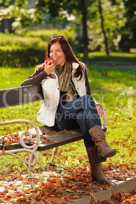 Autumn attractive woman eat apple sunset park