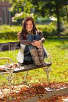 Autumn sunset park woman sitting on bench