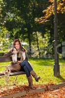 Autumn beautiful woman sit on bench park