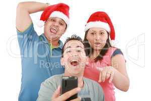 Young friends looking shocked at cell phone with Christmas hat