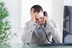 Close up of businessman getting bad news on the phone