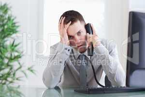 Close up of businessman getting sad news on the phone