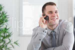 Businessman getting a pleasant call on his mobilephone