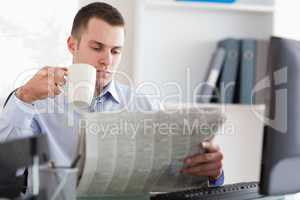 Businessman having a coffee while reading the newspaper