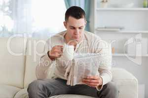 Man reading the news while drinking a coffee