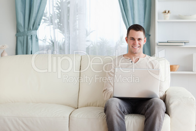 Man using a laptop while sitting on a sofa