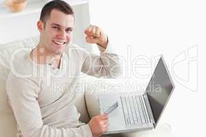 Young man shopping online with the fist up