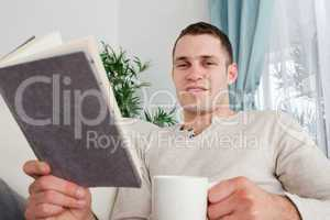 Man holding a cup of coffee and a book