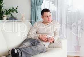 Pensive man holding a cup of coffee