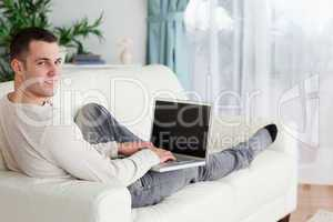 Man lying on his couch with a laptop