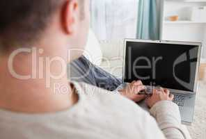 Man lying on his couch while using a laptop