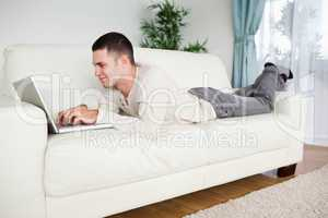 Handsome man lying on a couch using a notebook