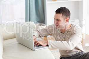 Smiling man sitting on a carpet while using a notebook
