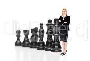 Businesswoman in front of black chess pieces