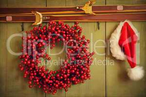 Red wreath with Santa hat hanging on rustic wall