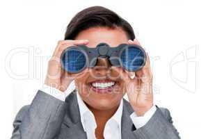 Assertive businesswoman looking through binoculars