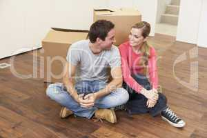 Young couple on moving day sitting with cardboard boxes