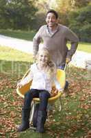 Father pushing child through autumn leaves on wheelbarrow