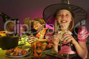 Halloween party with children having fun in fancy costumes