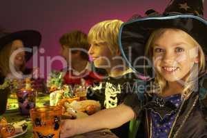 Halloween party with children having fun in fancy costumes