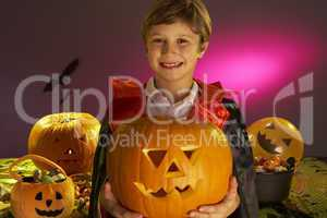 Halloween party with a boy child holding carved pumpkin