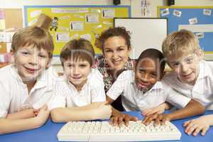 Schoolchildren in IT Class Using Computers with teacher