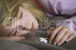 Depressed Teenage Girl Sitting In Bedroom With Pills