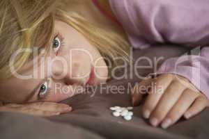 Depressed Teenage Girl Sitting In Bedroom With Pills
