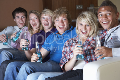 Group Of Teenage Friends Sitting On Sofa At Home Watching Drinki