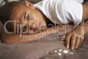 Depressed Teenage Boy Lying In Bedroom With Pills
