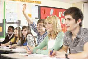 Teenage Students Studying In Classroom Answering Question