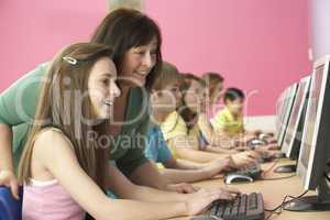 Teenage Students In IT Class Using Computers In Classroom With T