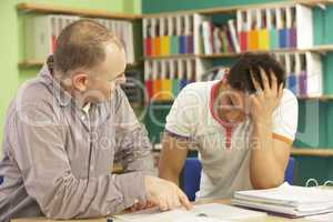 Teenage Student In Classroom With Tutor