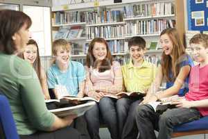 Teenage Students In Library Reading Books With Tutor
