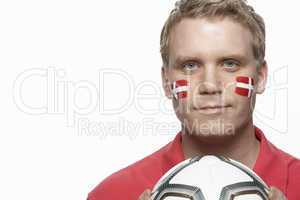Young Male Football Fan With Danish Flag Painted On Face