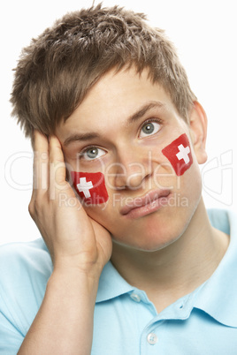 Disappointed Young Male Sports Fan With Swiss Flag Painted On Fa